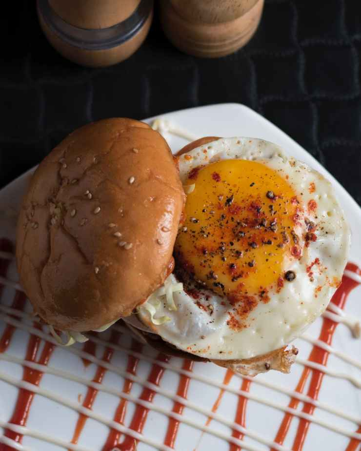 burger with sunny side up on white surface